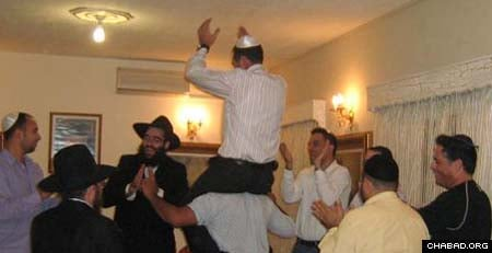 Chaim Harrari is lifted in a chair as Rabbi Arie Zeev Raskin, third from left, and others celebrate his Cypriot wedding.