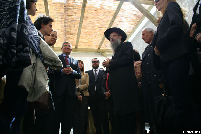 "Chabad-Lubavitch of Rome director Rabbi Yitzchak Hazan welcomes officials to the ""Sukkah of Peace"" erected for the Jewish holiday of Sukkot at the city's Piazza Farnese."